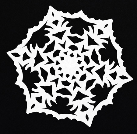 hand made cut out white snowflake on black paper background photo