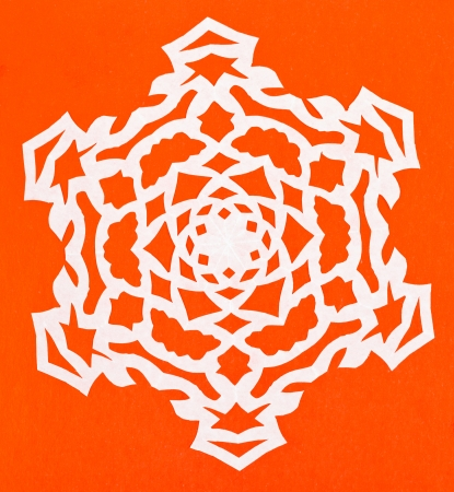 hand made cut out white snowflake on orange paper photo
