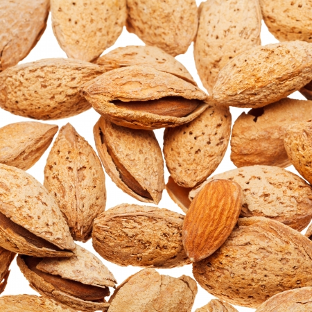 many fried almond nuts isolated on white background photo
