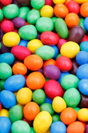 background from many multi-colored chocolate candy dragees close up photo