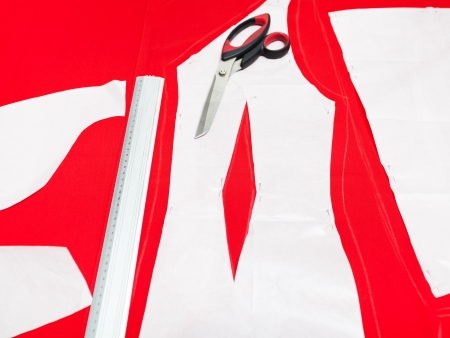 fitter scissors, ruler and cutting out woolen fabric along pattern lines for tailoring red dress photo