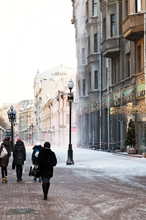 existed: MOSCOW, RUSSIA - JANUARY 19, 2014: tourists on Arbat street in winter morning. Arbat has existed since the 15th century, it is pedestrian street about one km long in historical centre of Moscow