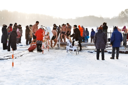 MOSCOW, RUSSIA - JANUARY 19, 2014: people near ice hole in frozen Akademicheskiy pond during traditional christening ice swimming in Orthodox church Holy Epiphany Day