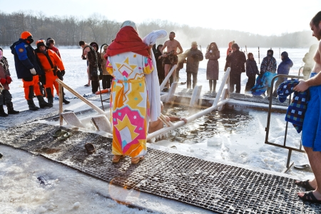 MOSCOW, RUSSIA - JANUARY 19, 2014: people near ice hole in frozen Akademicheskiy pond and traditional ice swimming in Orthodox church Holy Epiphany Day