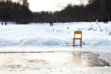 icebound chair near opening water in frozen lake after orthodox epiphany holiday in cold winter evening photo