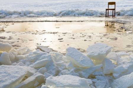 ice blocks and chair on edge of ice-hole in frozen lake in winter photo