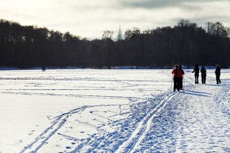 skiers and walking people on snowy field in cold winter sunny day photo