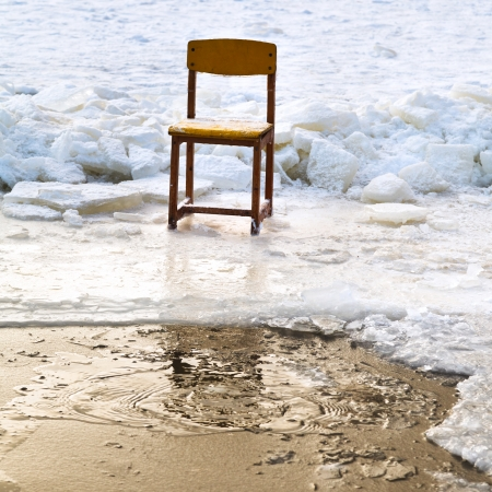 icebound chair on edge of ice-hole in frozen lake in winter photo