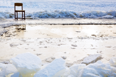 icebound chair near ice hole in frozen lake in cold winter day photo