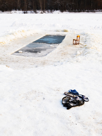 slippers and chair near ice hole in frozen lake in cold winter day photo