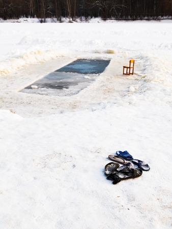 pila bautismal: zapatillas y silla cerca del agujero de hielo en el lago congelado en invierno frío día Foto de archivo