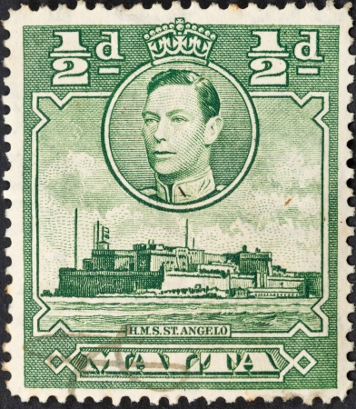 MALTA - CIRCA 1938: A green stamp printed in Malta shows King George VI and Fort St Angelo - large fortification in Birgu, Malta, circa 1938