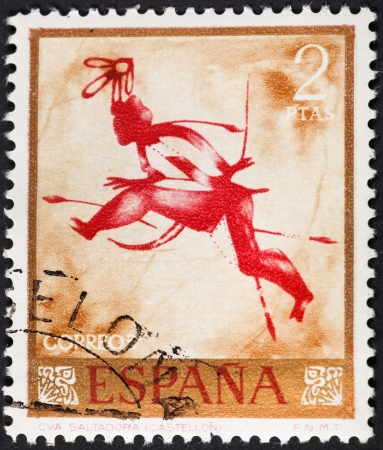 rock painting: SPAIN - CIRCA 1967: A postage stamp printed in the Spain rock painting of runing warrior in the Saltadora caves of Spain, circa 1967