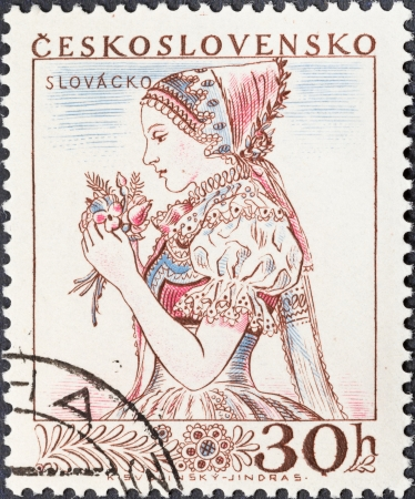 CZECHOSLOVAKIA- CIRCA 1956: A postage stamp printed in the Czechoslovakia shows portrait of young woman in Slovakian national costume, circa 1956