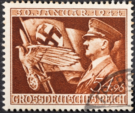 adolf: NAZI GERMANY - CIRCA 1944: A postage stamp printed in the Nazy Germany shows Adolf Hitler and symbols of Therd Reich, circa 1944