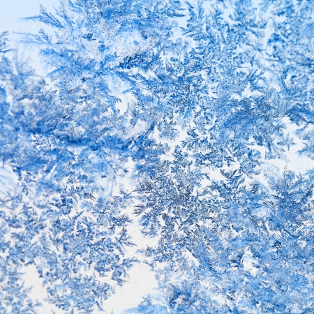 snowflakes and frost on glass close up - frosty blue pattern on window in cold winter day photo