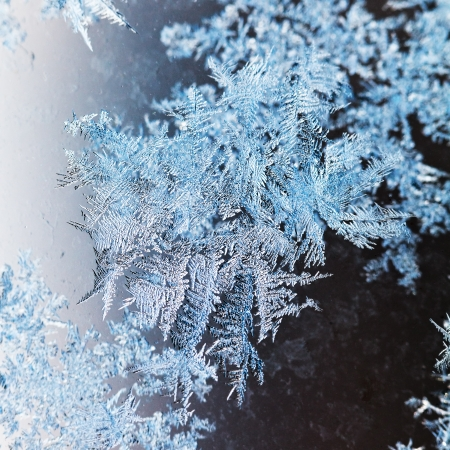 snowflakes and frost on glass close up - frosty blue and grey pattern on window in cold winter day photo