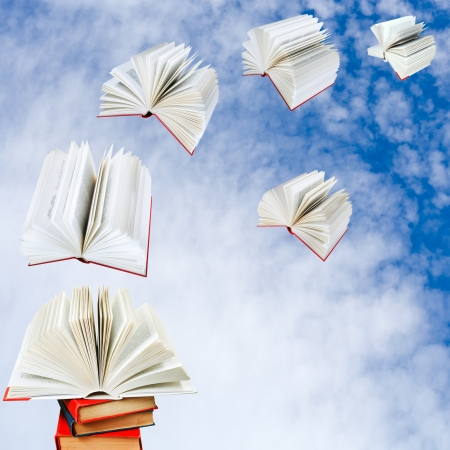double page spread: open books fly out of pile of books with cloudy blue sky background Stock Photo