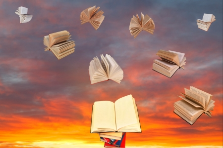 open book above of stack of books and sunset sky with flying books background photo