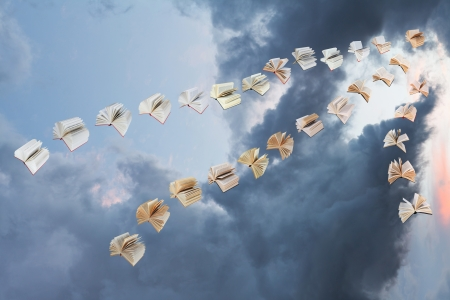 invented: flock of flying books with storm clouds background Stock Photo