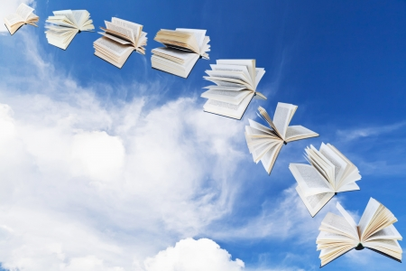 double page spread: arch of flying books with blue sky and white cloud background