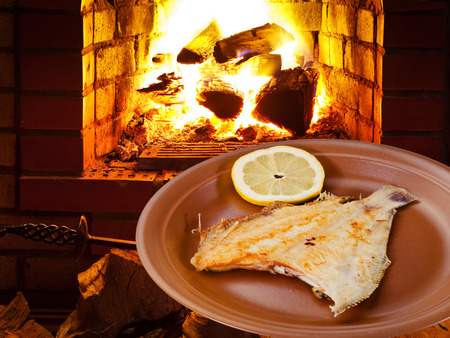 fried sole fish on plate and open fire in wood burning oven photo