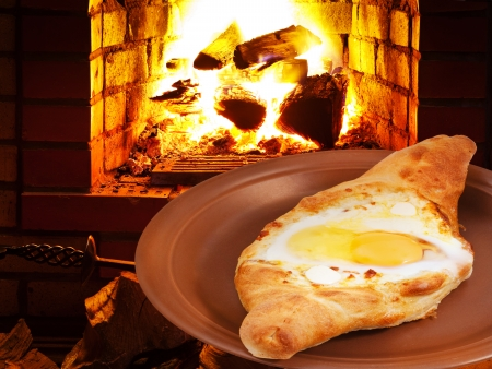 open topped: adzharia hachapuri with egg on plate and open fire in wood burning stove