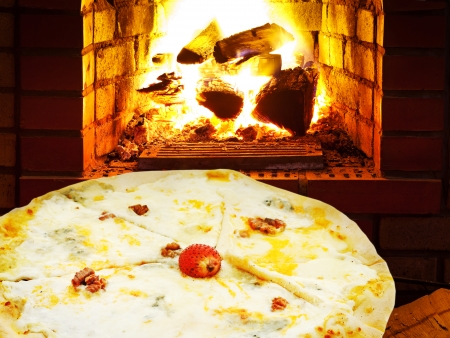 italian pizza quatro formaggi and open fire in wood burning oven photo