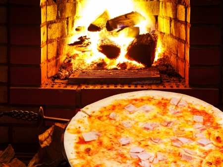 italian pizza with prosciutto cotto and open fire in wood burning oven photo