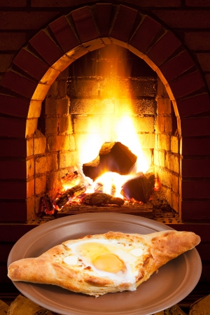 adzharian khachapuri with egg on plate and open fire in wood burning stove
