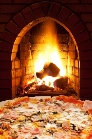 italian pizza with ham and mushrooms and open fire in wood burning stove photo
