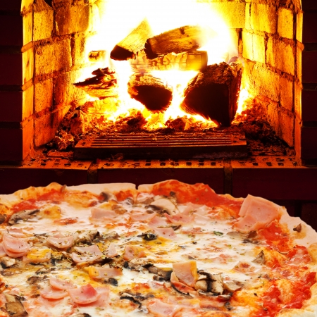 italian pizza with ham and mushrooms and open fire in wood burning oven photo