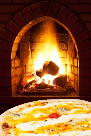 italian pizza quatro formaggi and open fire in wood burning stove photo