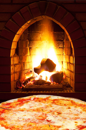 italian pizza margherita and open fire in wood burning oven photo