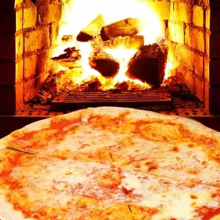 italian pizza margherita and open fire in wood burning stove photo