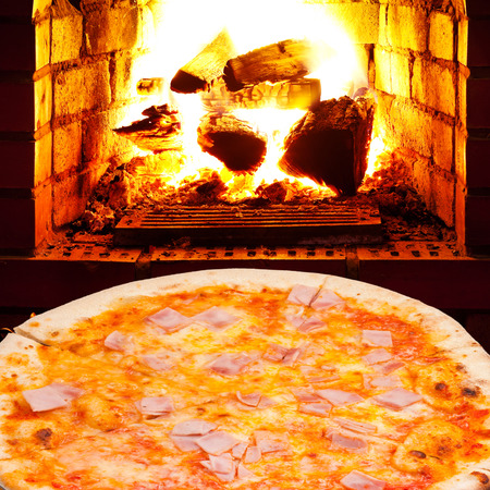italian pizza with prosciutto cotto and open fire in wood burning stove photo