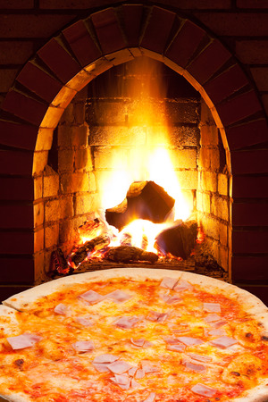 italian pizza with ham and open fire in wood burning oven photo