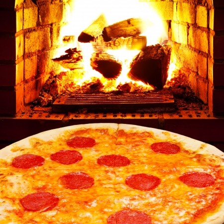 italian pizza with salami and open fire in wood burning stove photo