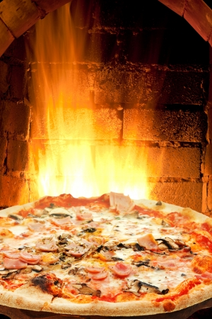 pizza oven: italian pizza with ham and mushrooms and fire flames in wood burning oven