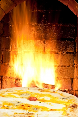italian pizza and fire flames in wood burning oven photo