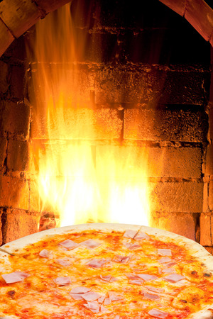 italian pizza with prosciutto cotto and fire flames in wood burning oven photo