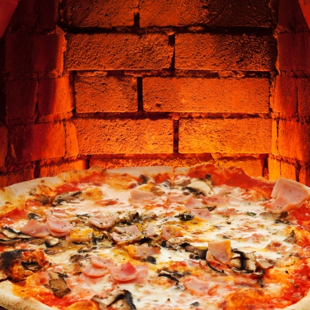 italian pizza with ham and mushrooms and hot brick wall of wood burning oven photo