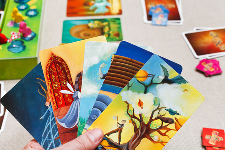 spiel: MOSCOW, RUSSIA - FEBRUARY 3, 2014: playing in Dixit card game. The game was created by Jean-Louis Roubira in 2008, and in 2010 the game received prestigious award Spiel des Jahres (Game of the Year)