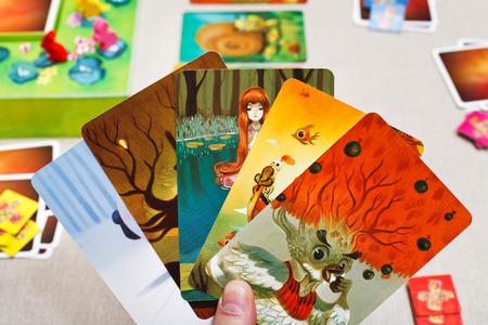 jeu de carte: MOSCOU, RUSSIE - 3 février 2014: Dixit cartes de jeu à la main. Le jeu a été créé par Jean-Louis Roubira en 2008, et en 2010, le jeu a reçu le prix prestigieux Spiel des Jahres (Jeu de l'Année)