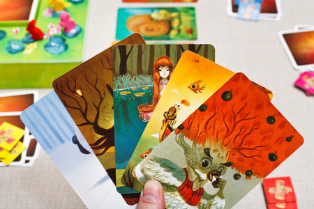 card game: MOSCOW, RUSSIA - FEBRUARY 3, 2014: Dixit game cards in hand. The game was created by Jean-Louis Roubira in 2008, and in 2010 the game received prestigious award Spiel des Jahres (Game of the Year) Editorial