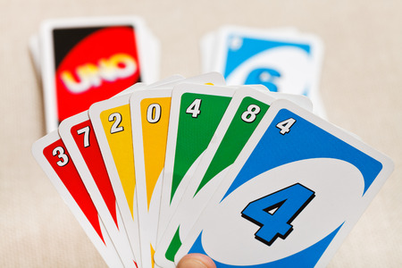 MOSCOW, RUSSIA - FEBRUARY 3, 2014: Uno card game in player hand. The game was developed by Merle Robbins in USA in 1971, and it has been Mattel product since 1992