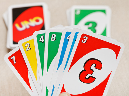 card player: MOSCOW, RUSSIA - FEBRUARY 3, 2014: view of Uno card game pack in hand. The game was developed by Merle Robbins in USA in 1971, and it has been Mattel product since 1992