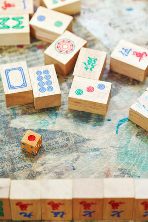 playing in mahjong game by wooden tiles on shabby table close up photo