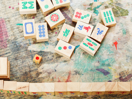 playing in mahjong game by wood tiles on shabby table closeup photo