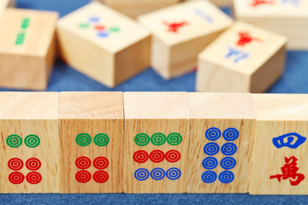wood tiles closeup in mahjong game durung playing on blue cloth table photo